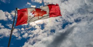 An image of the Canadian flag blowing in the wind against a backdrop of clouds