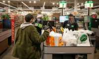 A cashier wearing a face shield for protection against the deadly new coronavirus bags groceries for a customer at the Local Market Foods store in Chicago.  By KAMIL KRZACZYNSKI (AFP)