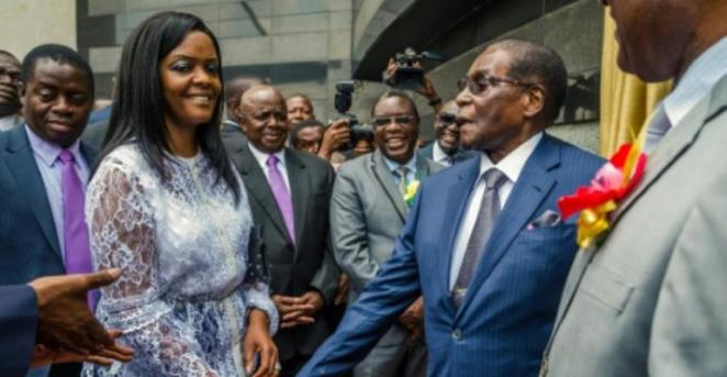 Zimbabwean President Robert Mugabe (R) is congratulated by his wife, First Lady Grace Mugabe, after he unveiled a plaque at the country's main international airport in Harare, Zimbabwe, renamed after him on November 9, 2017.  By Jekesai NJIKIZANA (AFP)