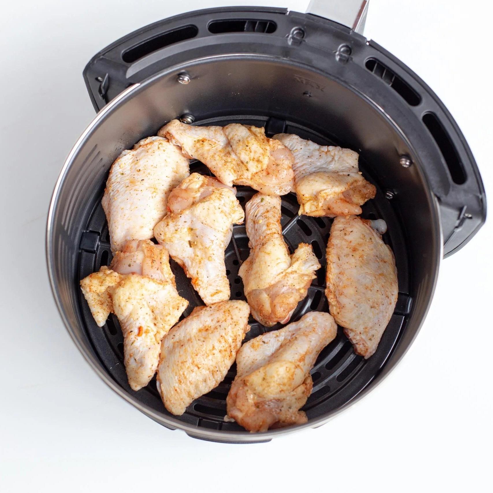 Seasoned chicken wings in an air fryer