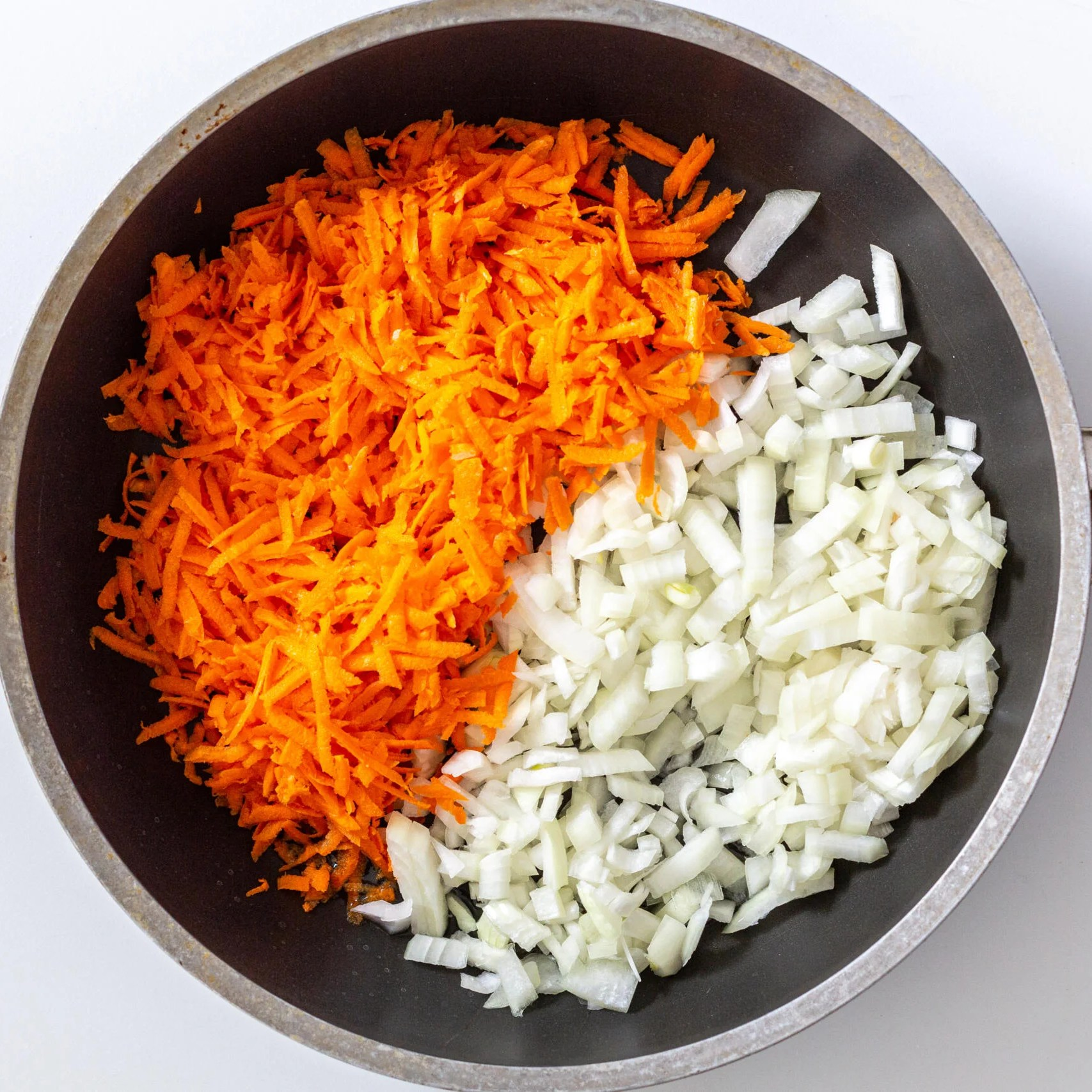 onion and carrot on a skillet