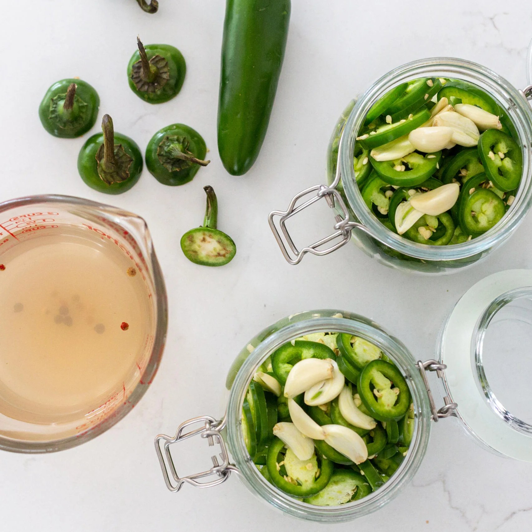 sliced Jalapenos with marinade and jars