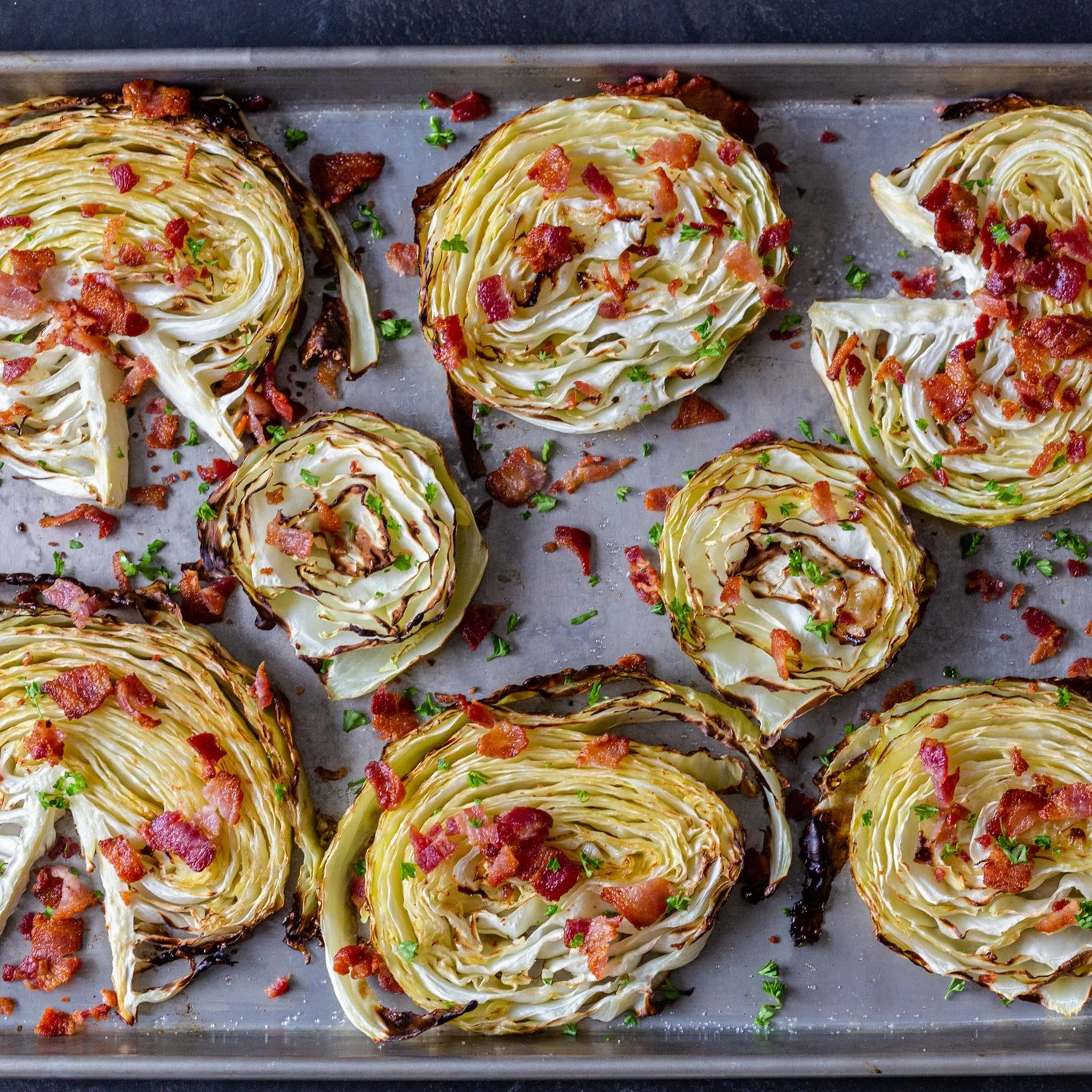 crispy roasted cabbage steaks on a pan with bacon