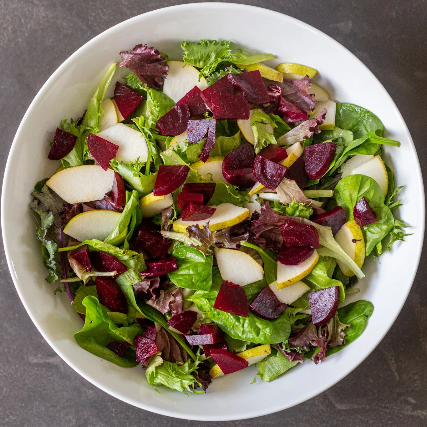 green leaves, pear and beets in a bowl