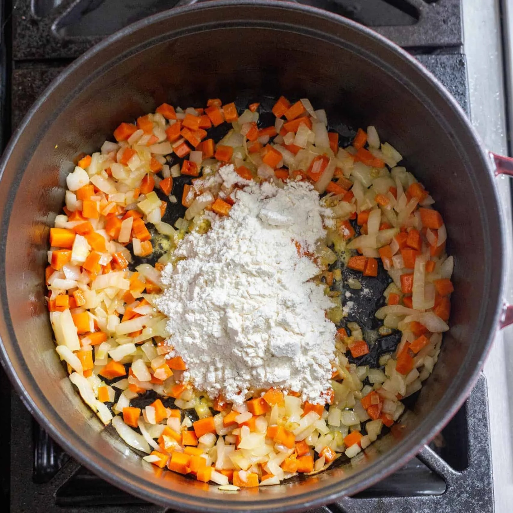 sauteed onions and carrots with flour in the pot