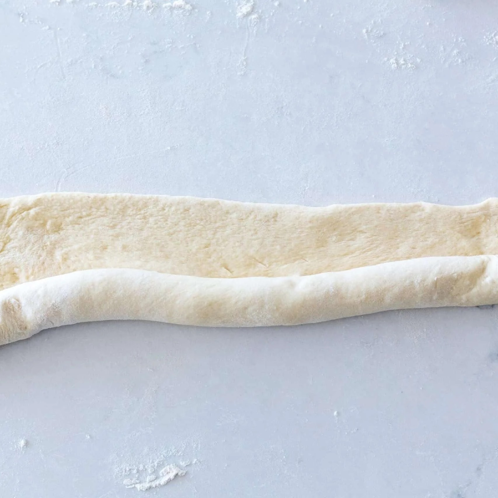 bread dough on a counter rolled up