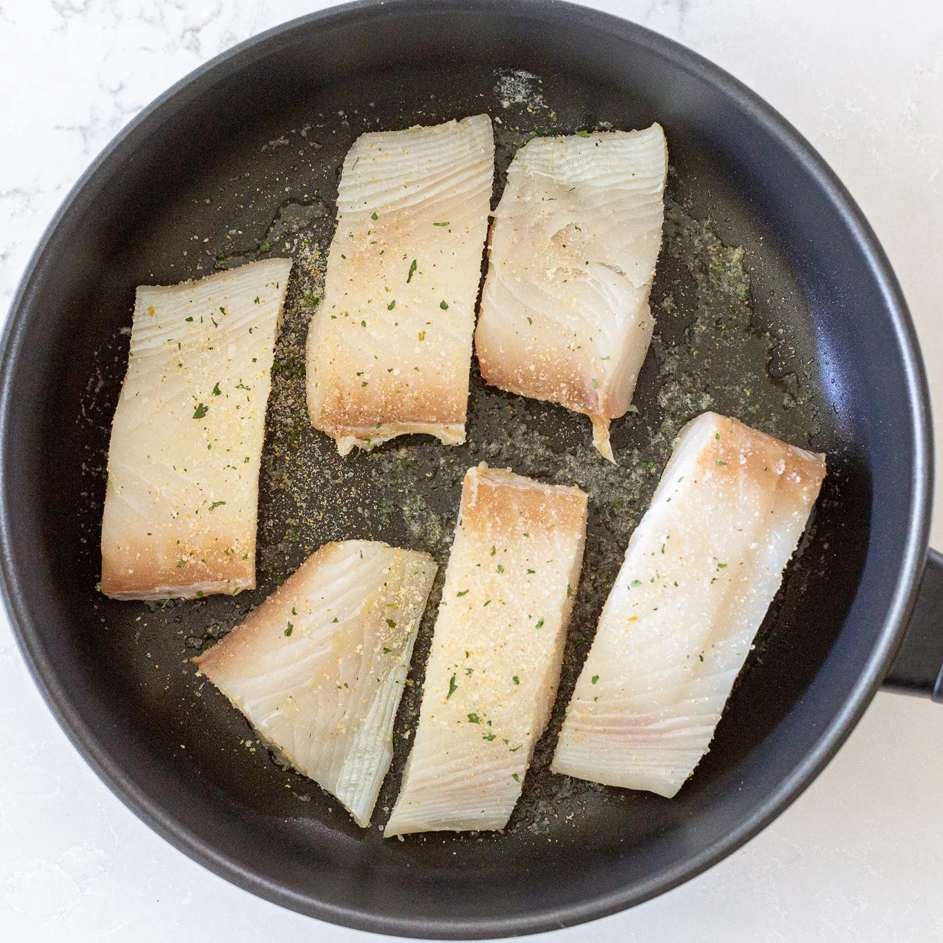 halibut cooking in a pan
