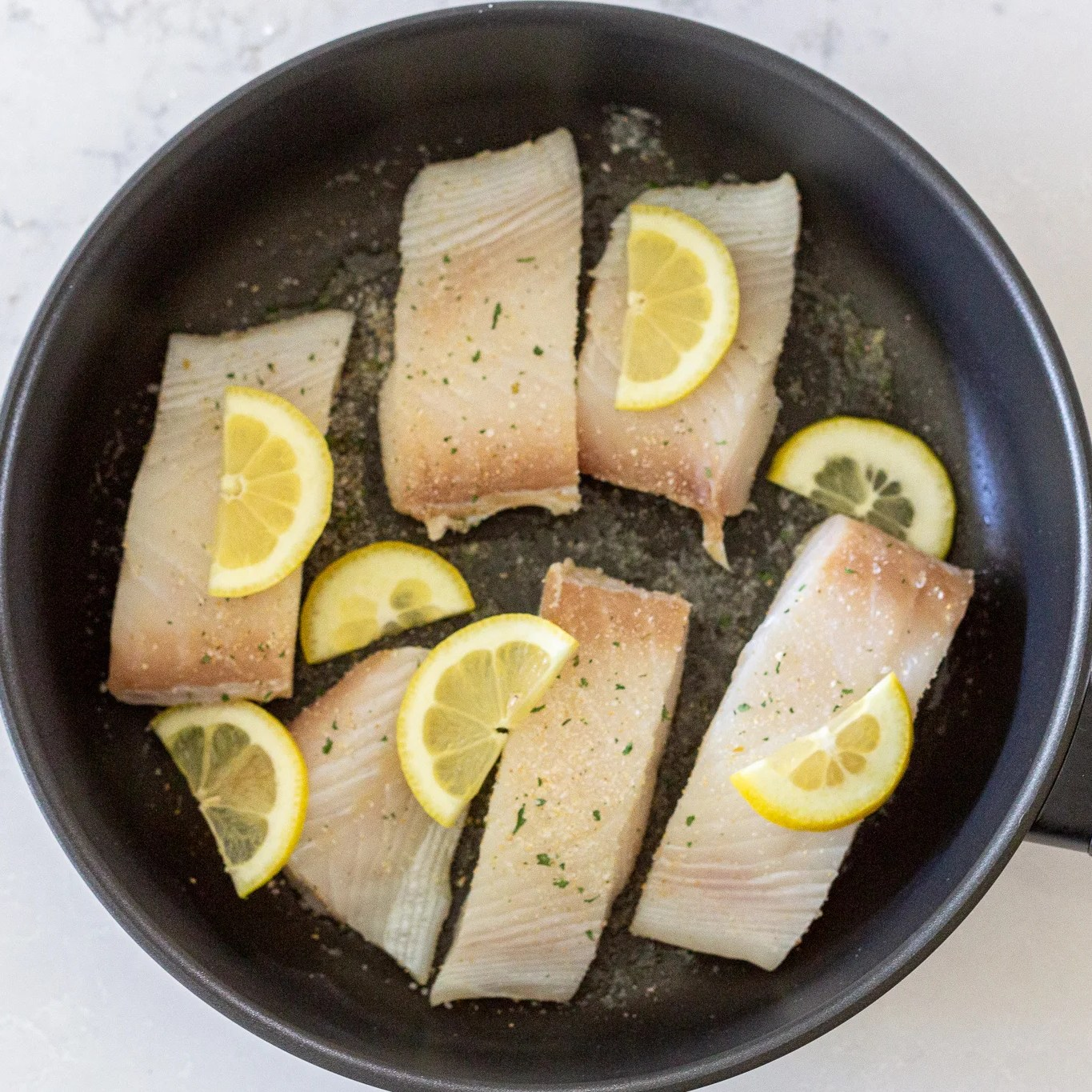 halibut with lemon and seasoning in a pan