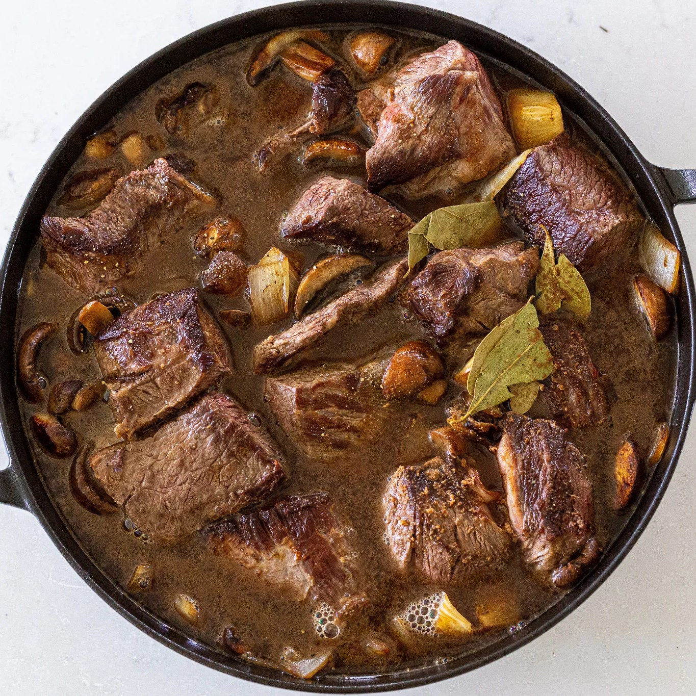 beef with broth and seasoning in a pan