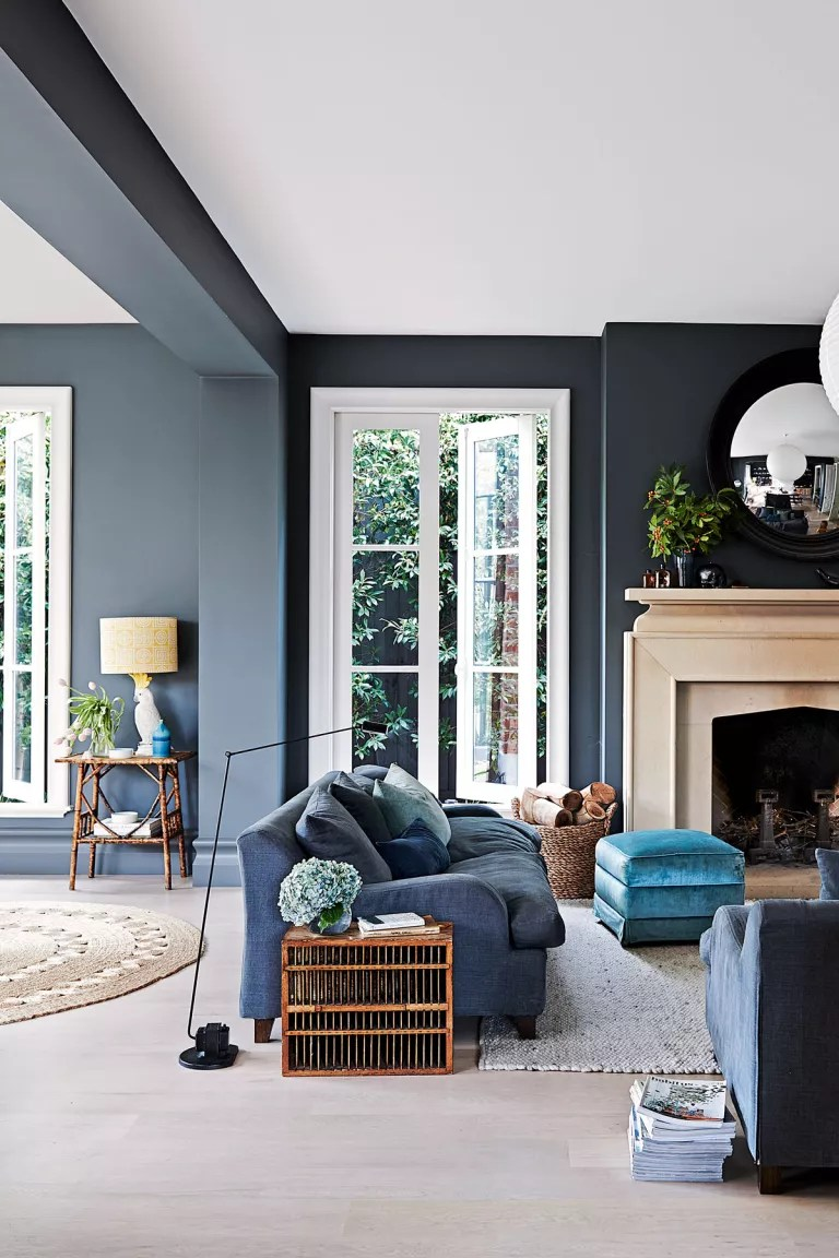 Dark blue living room with white ceiling, blue sofa and stone fireplace