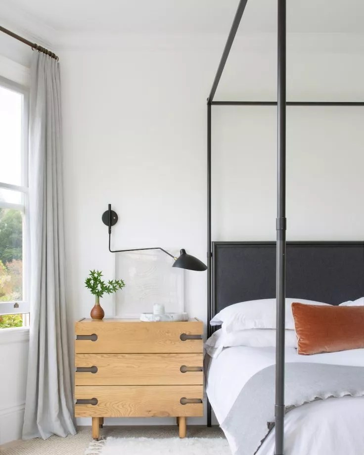 modern master bedroom with black four poster bed and and modern lighting
