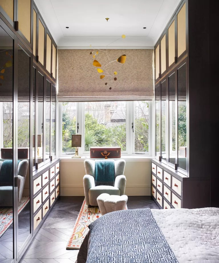 A walk-in closet area in a bedroom with double gallery cabinets and drawers