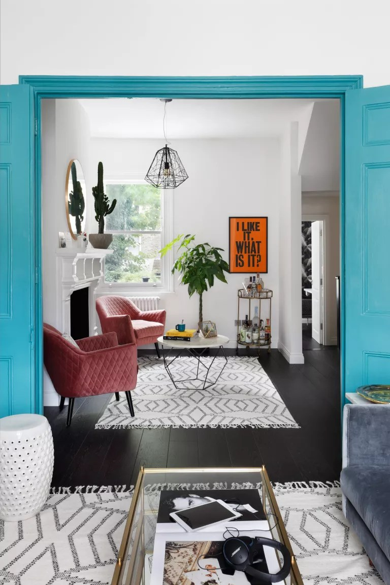 Open plan living room with blue accents and pink chairs