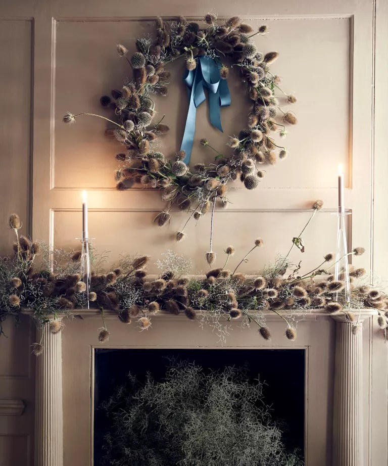 Fall mantel ideas with dried thistles covering the mantel and forming a wreath with a blue ribbon