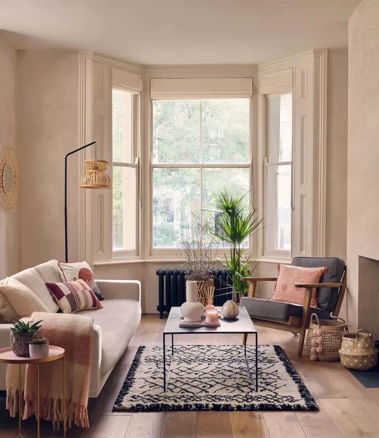 Neutral living room with boho, rattan accents, berber high pile rug, black coffee table, cream couch with wool throw, small rose gold side table and gray armchair with small pink cushion