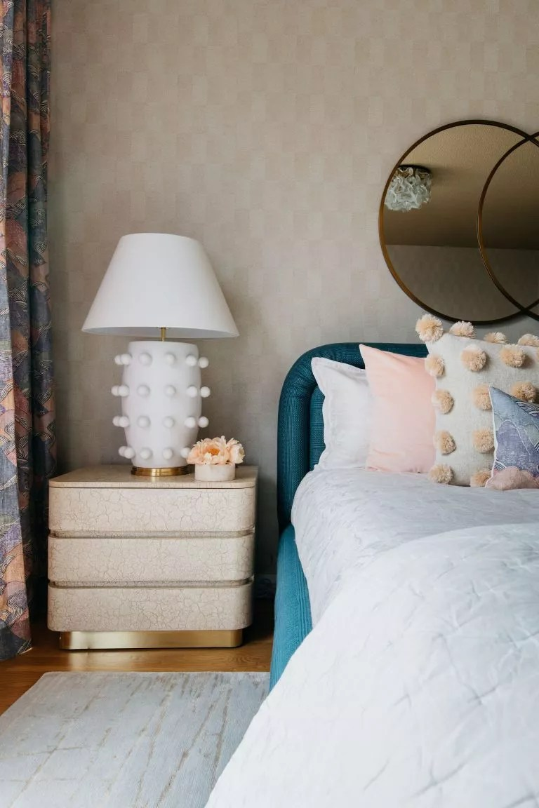 master bedroom with teal headboard and pink cushions
