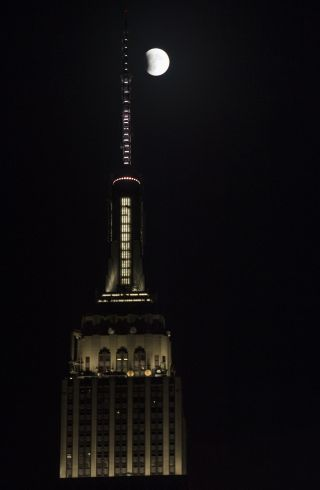 The full moon is seen next to New York City's Empire State Building at the beginning of a total lunar eclipse on Sept. 27, 2015.