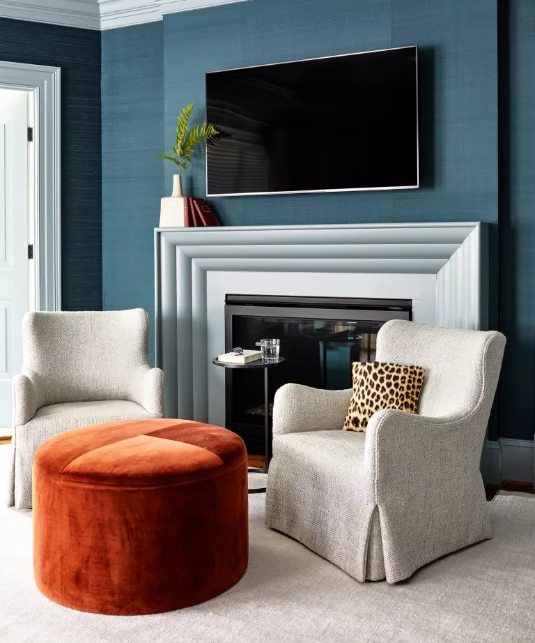 A bedroom with blue walls, two white armchairs and an orange velvet storage ottoman