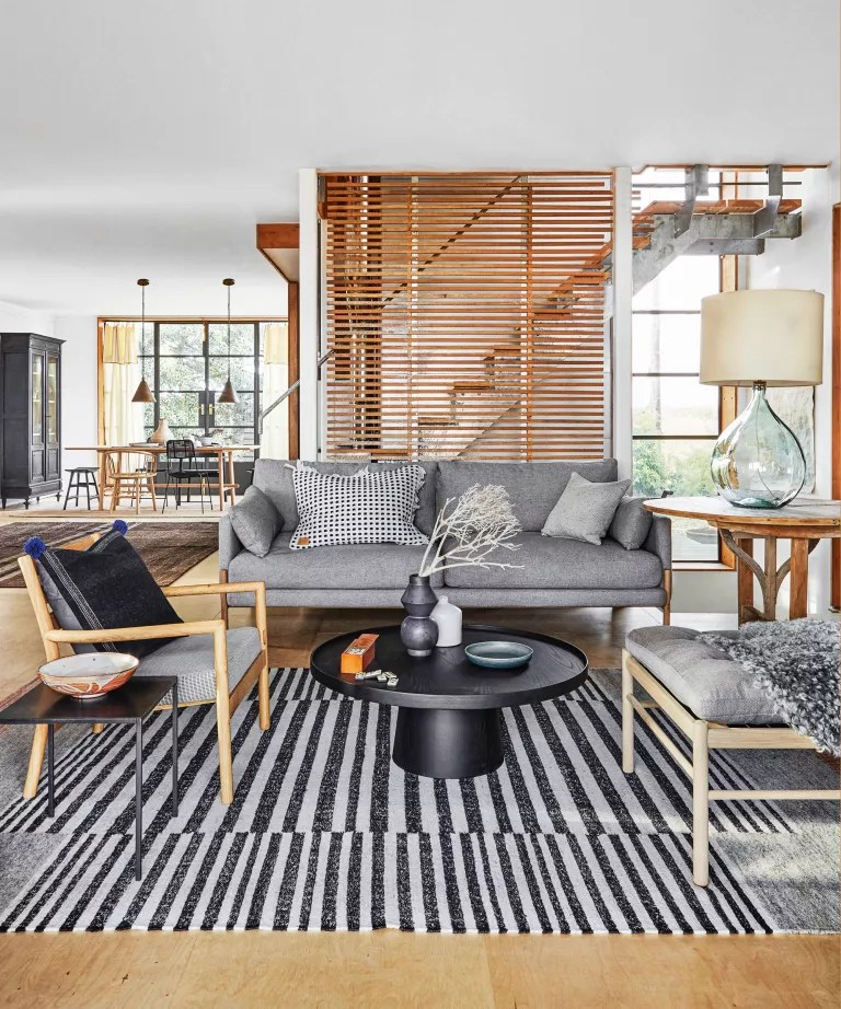 A living room with grey sofa, wooden furniture and black and grey striped rug
