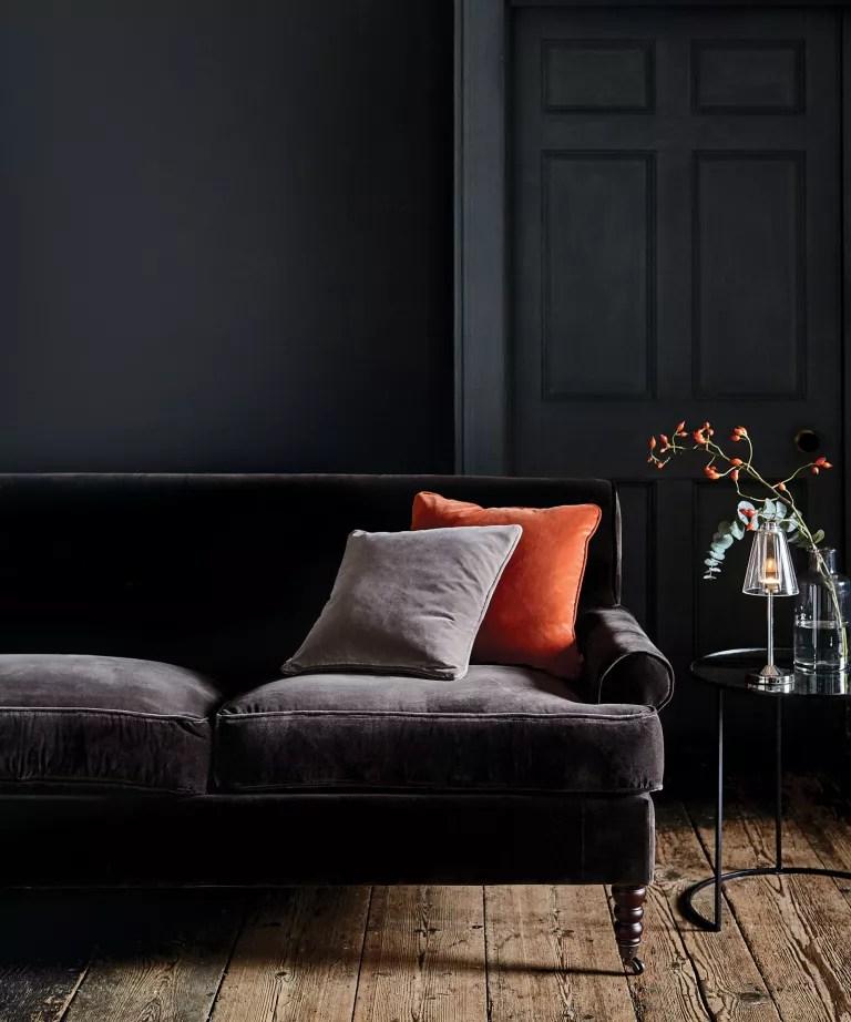Black living room with velvet sofa