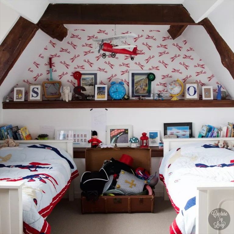 Attic shared bedroom ideas featuring a red aeroplane wallpaper, blankets and toy hanging from ceiling, built-in wooden shelving and a storage trunk.
