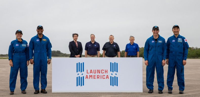 A crew arrival event for NASA's SpaceX Crew-1 mission is held Nov. 8, 2020, at the Launch and Landing Facility at the agency's Kennedy Space Center in Florida. From left are NASA astronaut Shannon Walker, mission specialist; NASA astronaut Victor Glover, pilot; Junichi Sakai, manager, International Space Station Program, JAXA; NASA Administrator Jim Bridenstine; NASA Deputy Administrator Jim Morhard; Bob Cabana, director, Kennedy Space Center; NASA astronaut Michael Hopkins, spacecraft commander; and JAXA astronaut Soichi Noguchi, mission specialist.