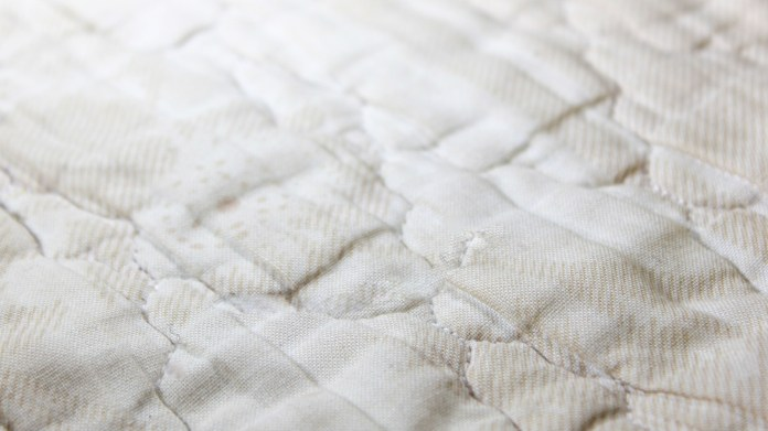 A white mattress with yellow spots on top
