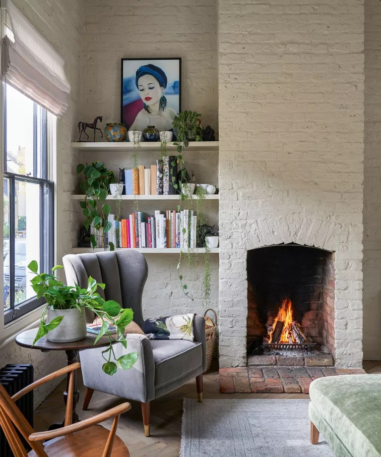 Living room fall decor with fireplace, brick wall and shelving