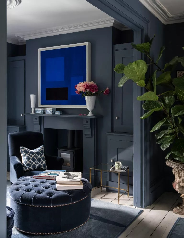 Dark blue living room with fireplace and foot stool