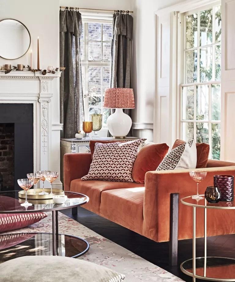 A living room curtain idea with orange velvet sofa and grey fold top curtains