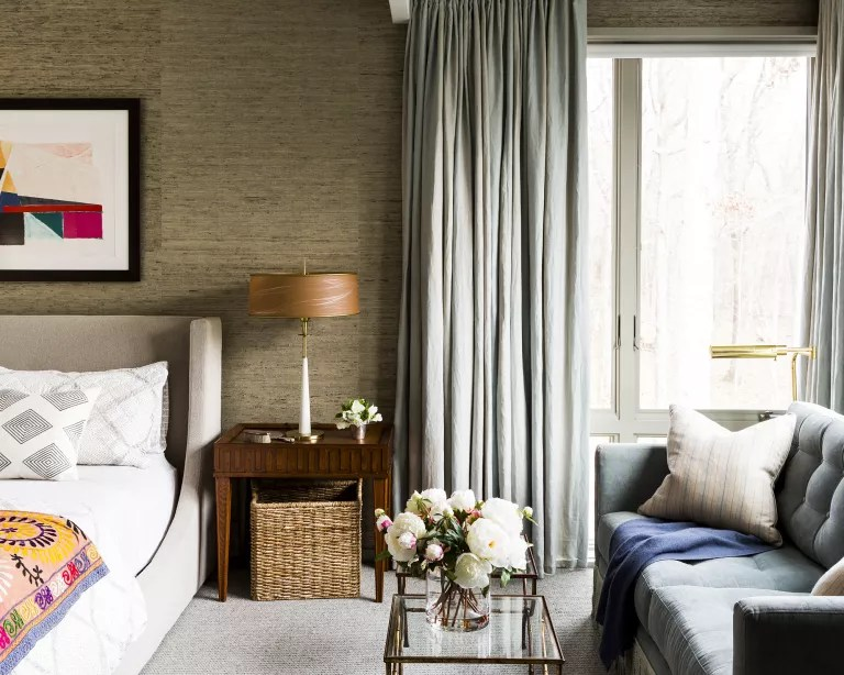A bedroom with woven basket storage under the bedside table, a sofa and large bay windows