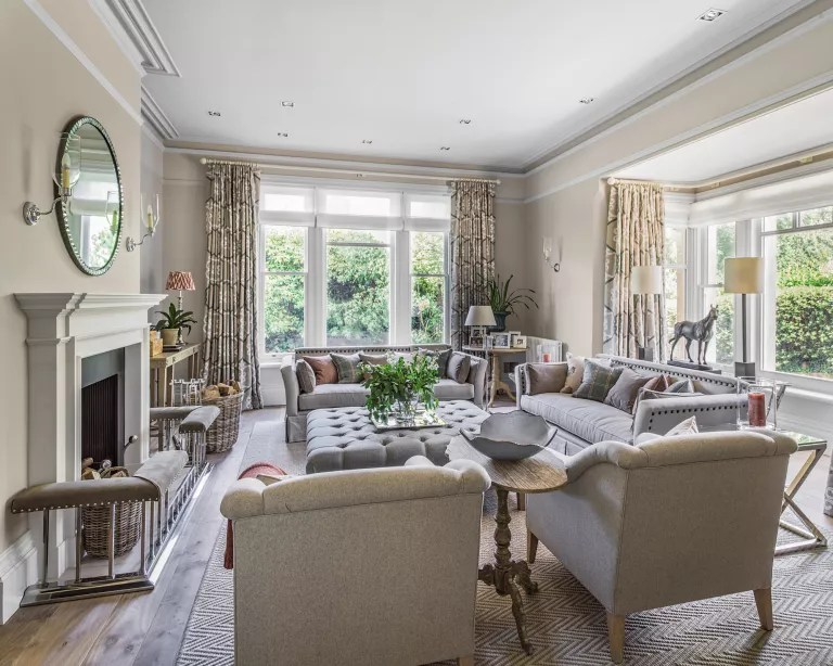 A living room with grey sofa. beige walls and traditional style fireplace
