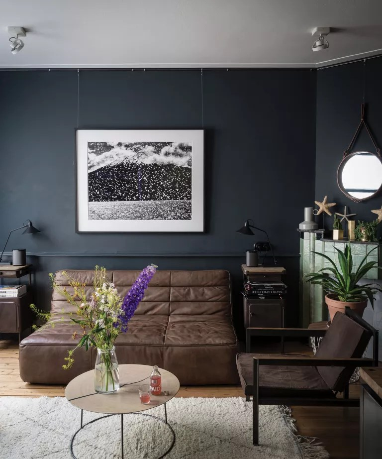 Black living room with brown leather sofa