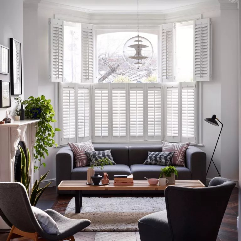 Wooden bay window shutters frame dark living room sofa and armchairs with house plants on mantle