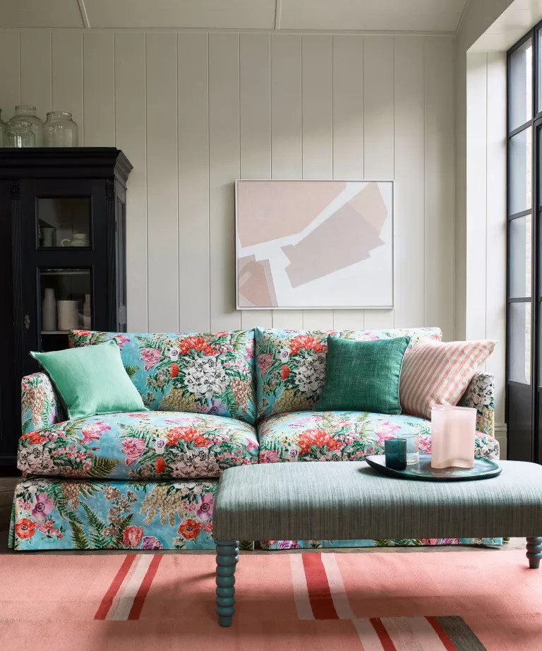 living room with blue floral sofa pink rug and black cabinet and artwork