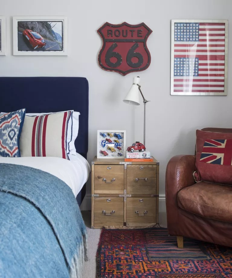 A bedroom with red and blue furnishings and artwork, with an aged leather armchair
