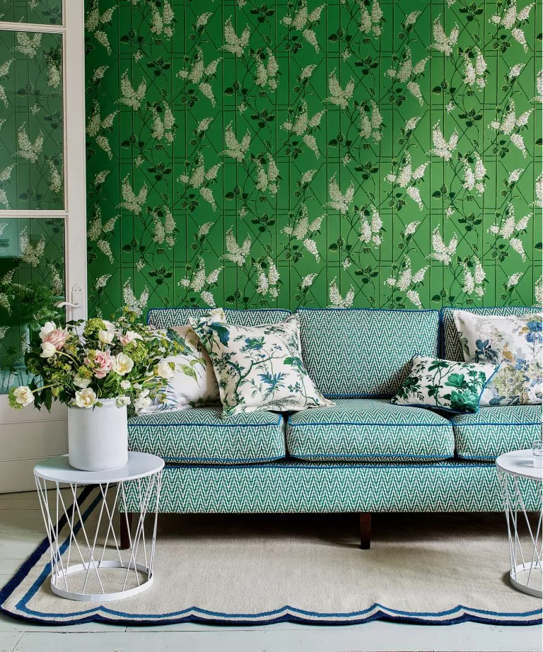 A bright green floral and geometric patterned wallpaper behind a blue sofa and neutral accessories.
