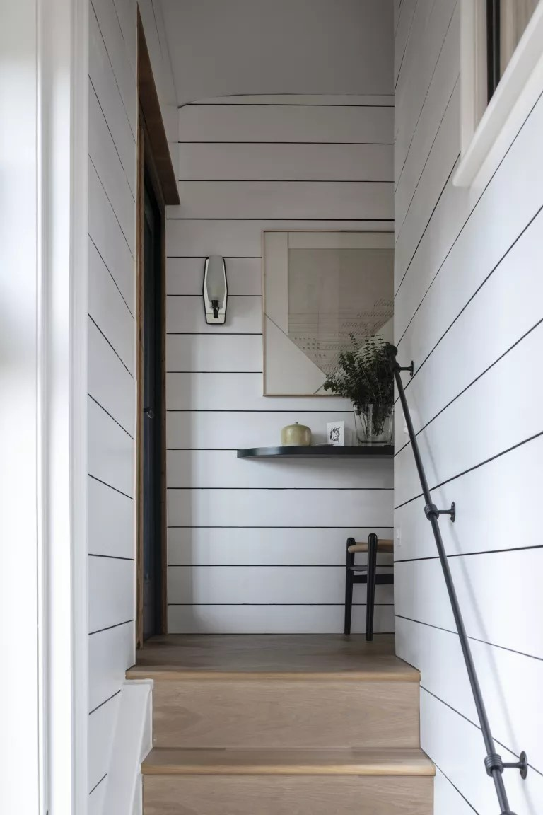 white hallway and stairs with white shiplap walls