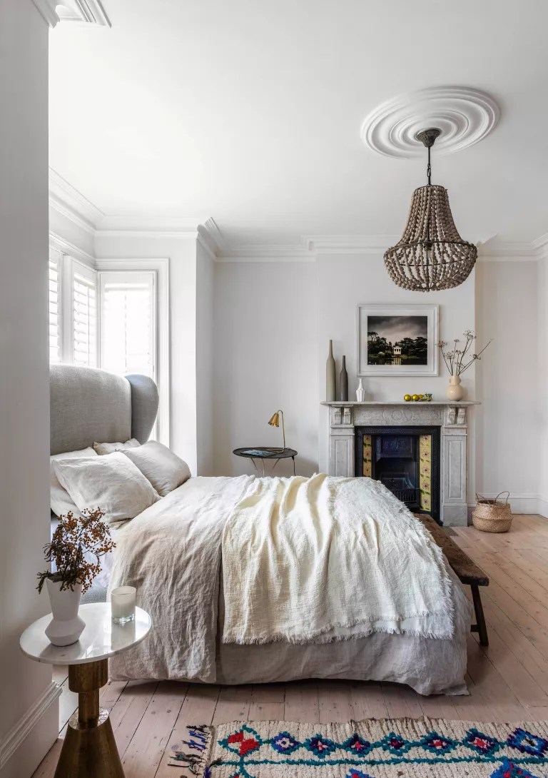 White bedroom with boho touches and large chandelier