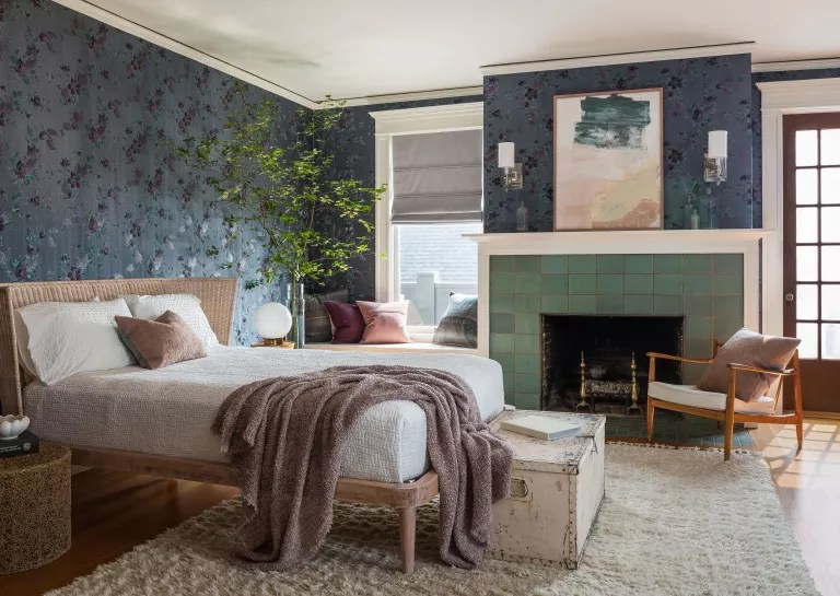 Bedroom with dark blue embroidered wallpaper and green tiled fireplace