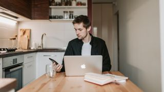 A casually-dressed man in a kitchen with a laptop, working from home.