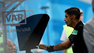 A referee checking a VAR situation. (Credit: Maja Hitij - FIFA/FIFA via Getty Images)