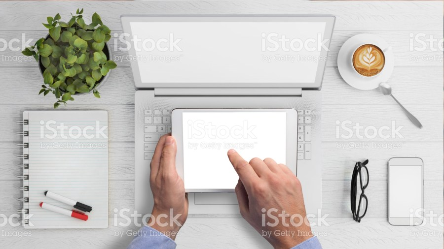 Blank laptop and tablet with man tapping screen