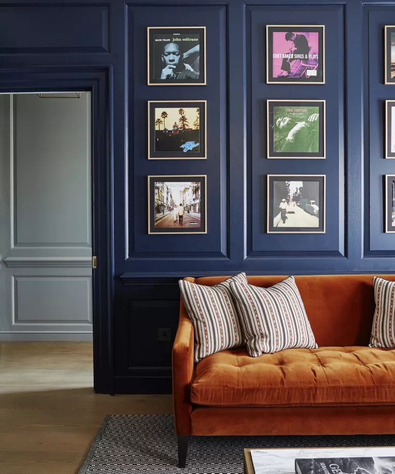 A living room with navy blue panelled walls and a burnt orange velvet sofa