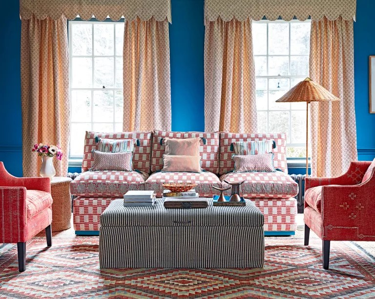 A living room curtain idea with blue walls, red and white sofa, and cream curtains with pelmet