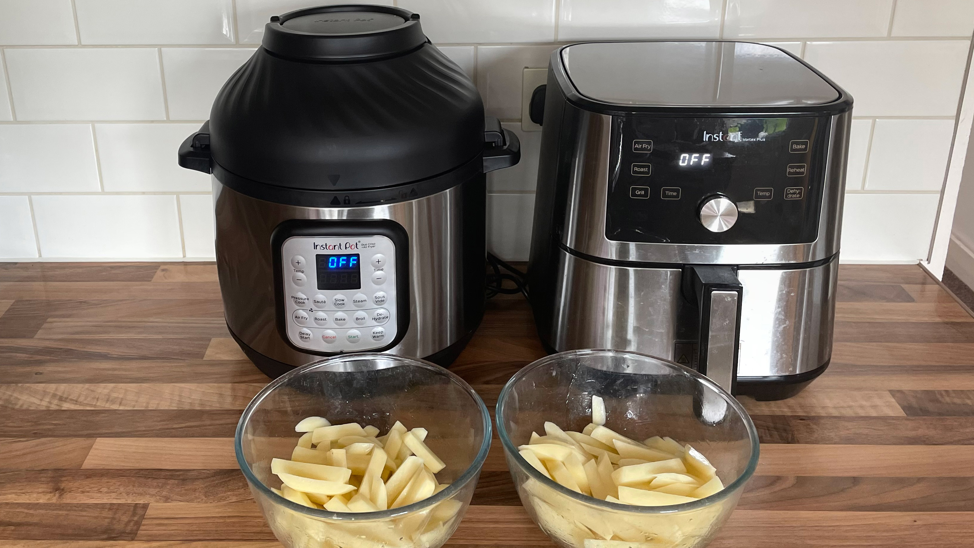 An Instant Pot Duo Crisp & Air Fryer with an Instant Vortex Plus air fryer on a kitchen counterytop and bowl of potato ready to be air fried into fries
