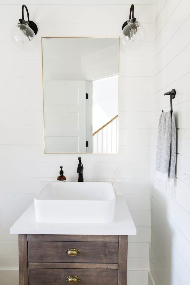 white painted bathroom with white shiplap walls black fixtures and fittings and brass mirror