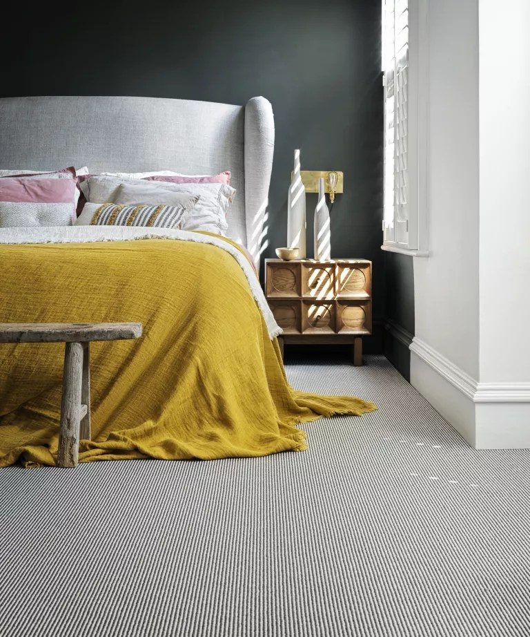 A bedroom with black walls, a white bed with yellow throw, and black and white striped carpet