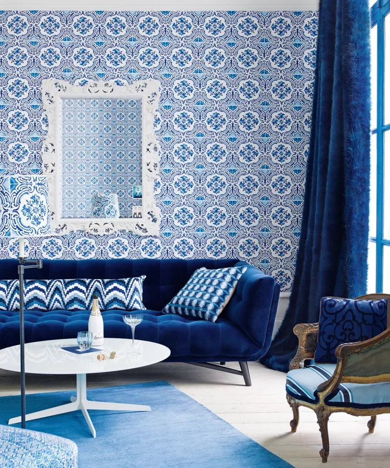 A living room with a dark blue sofa and wallpaper in the style of Portuguese blue and white tiles