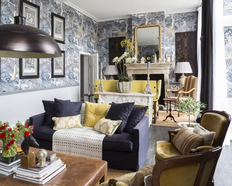 A traditional living room with pale blue wallpapered walls, and a navy blue sofa with yellow soft furnishings